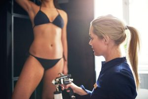 cosmetologist spraying tan bodypaint on woman
